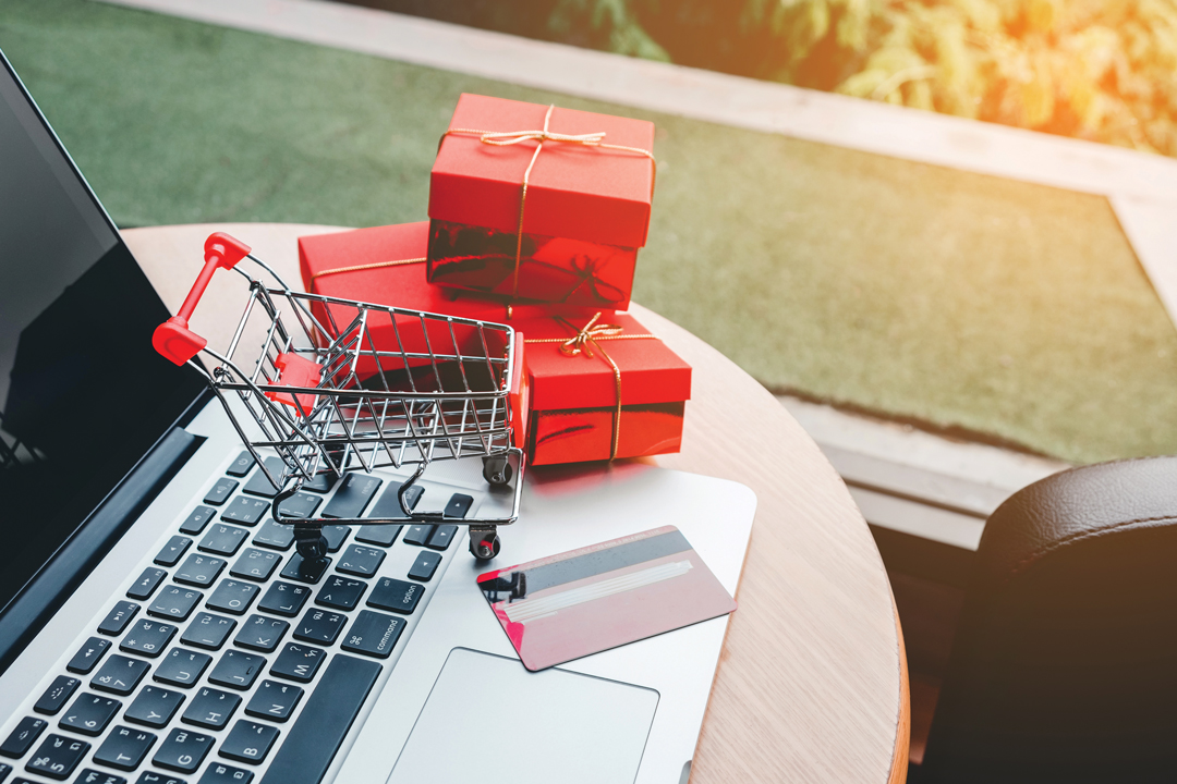 A laptop with credit card, toy shopping cart and three small red wrapped presents to help visualize online shopping.