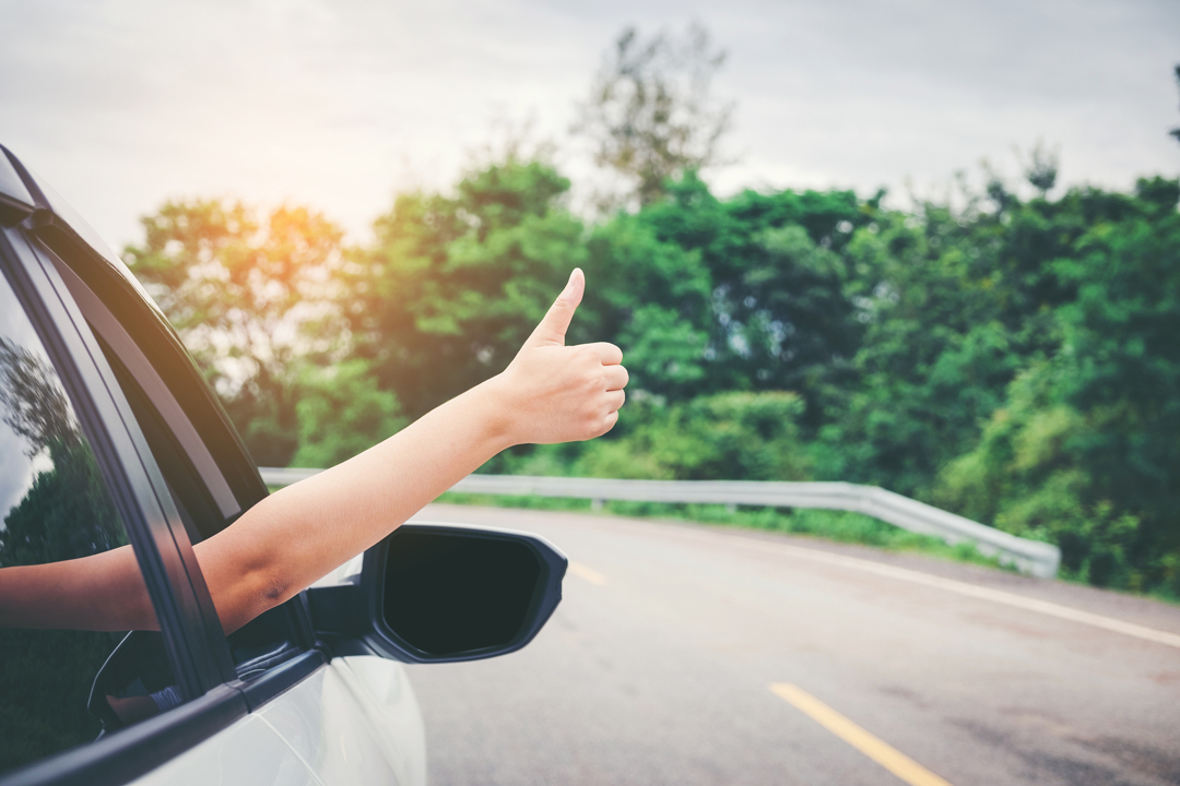 Close up of passenger side of a traveling vehicle with a woman giving a thumbs up signal.