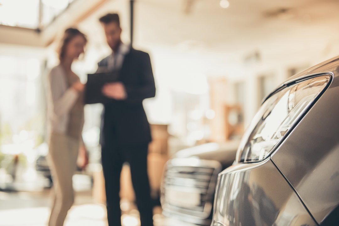 Close up view of vehicle in dealer showroom with man and woman in background